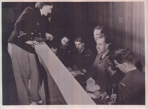 Lieutenant Carol Hendry (standing) and comrades shown plotting positions on tactical table during a tactical game, 1944. Slacks were only worn on the job due to the the amount of time spent on the floor.