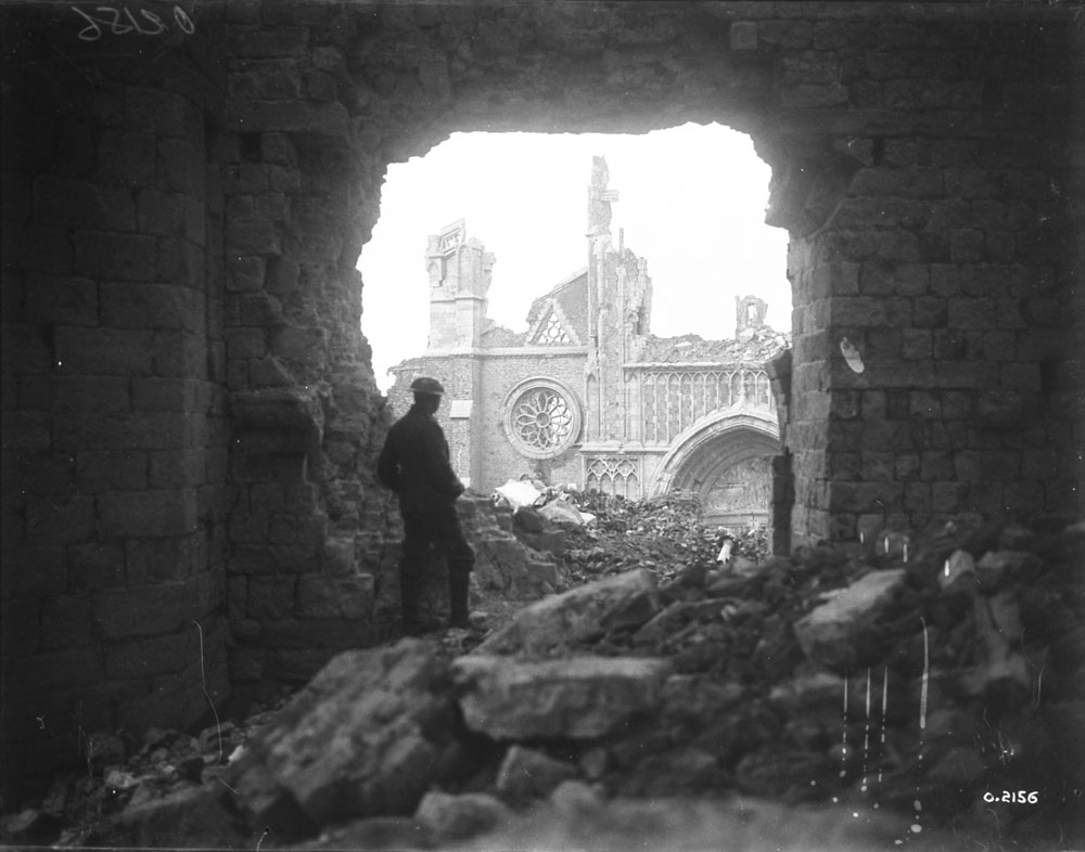 A Canadian soldier looking through the south entrance of the Cathedral in Ypres, 1917.