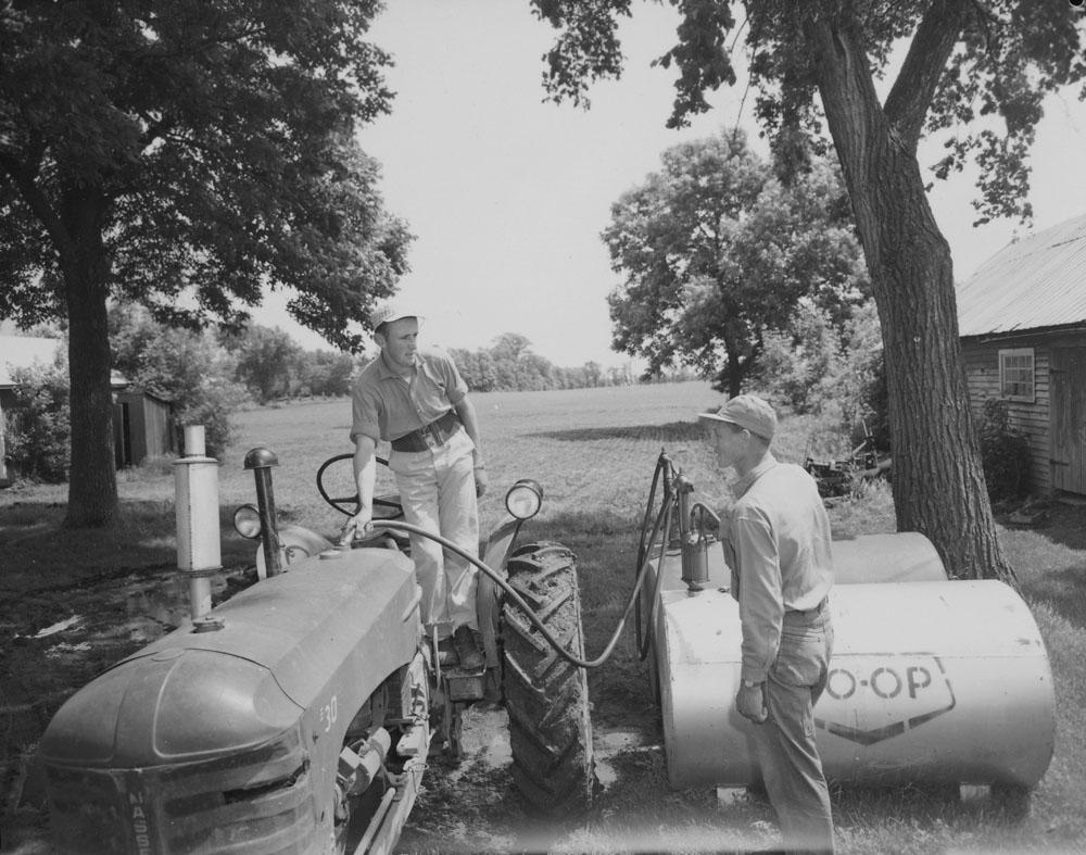 Deux travailleurs belges qui pompent du carburant dans un tracteur sur une ferme canadienne