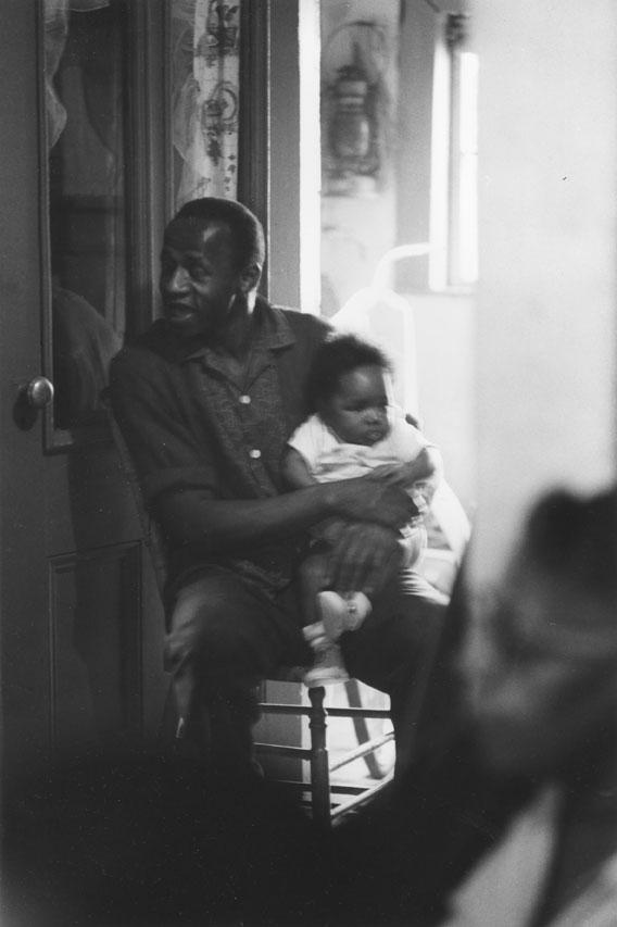 Homme tenant un bébé sur ses genoux, 1965.