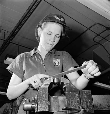 Woman factory worker files a machine part while piped music plays on loudspeakers, November 1943.