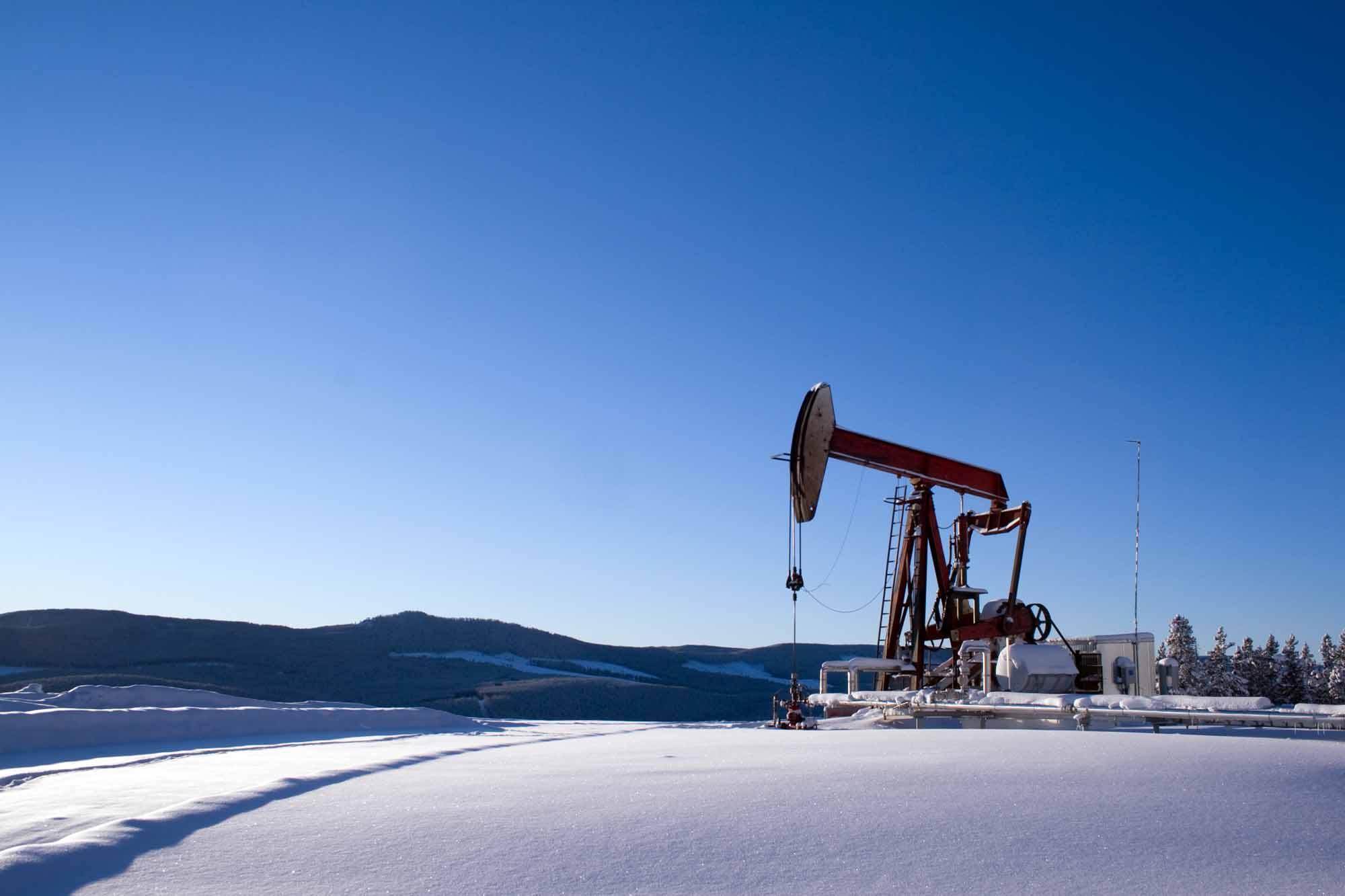 Oil well pumpjack mountain snow