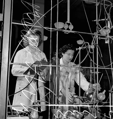 Two female laboratory workers test synthetic rubber in the Polymer Rubber Corporation plant, January 1944.
