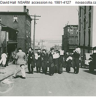 Sailors carrying spoils of the V-E Day Riot walking up or westerly along Salter Street between Hollis and Granville