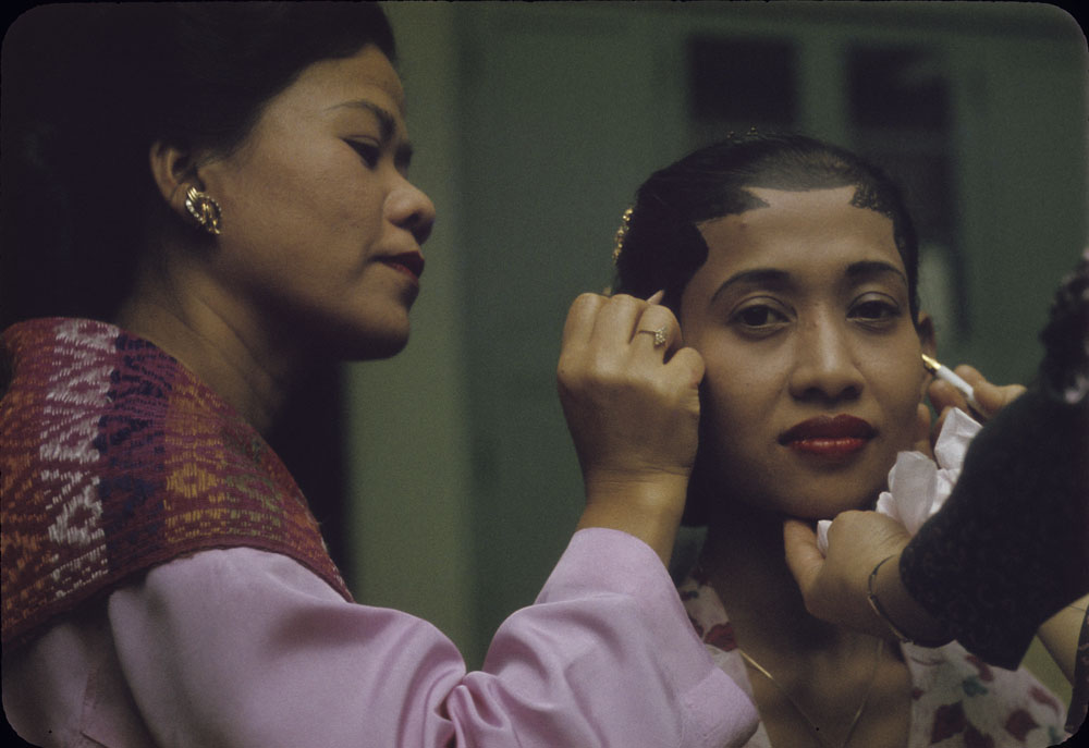 """""""Asian Evening"""" at Friendship House, Ottawa - Indonesian woman having makeup applied for a performance (1963)"""