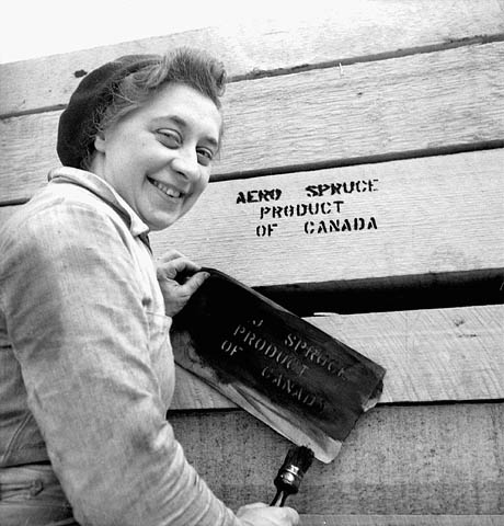 """Unidentified """"lumberjill"""" painting """"Aero Spruce Product of Canada"""" stencil on a pile of lumber, April 1943."""