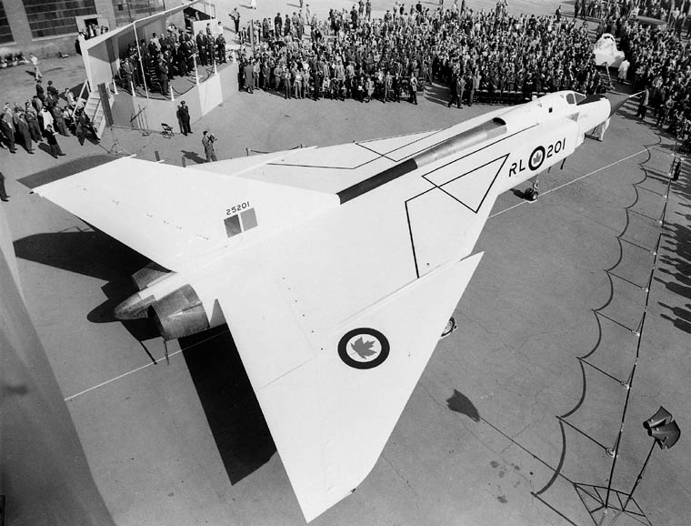 A crowd of people gathered on tarmac around the Avro Arrow at its unveiling in 1957.