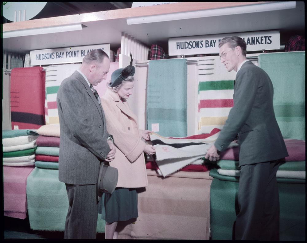 Examining blankets at the Hudson's Bay Company (Winnipeg, Manitoba, 1949).