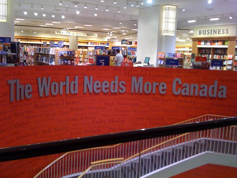 """Photograph taken inside the Indigo store at the Eaton Centre in Toronto, Ontario. The words """"The World Needs More Canada"""" run along a wall displaying the names of Canadian authors."""