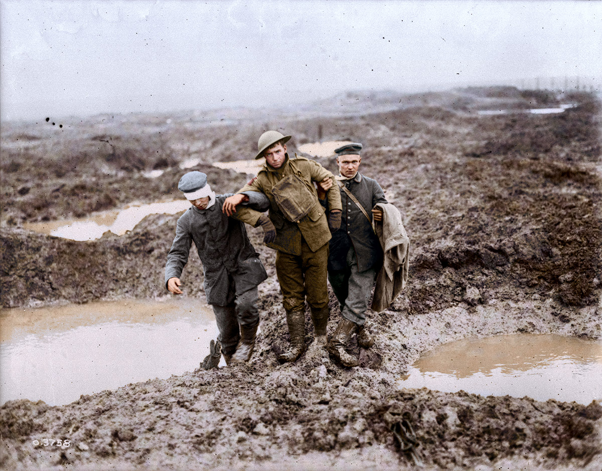 Canadian and German soldiers help one another through the mud during the capture of Passchendaele. November, 1917.