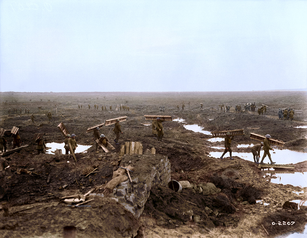 Canadian Pioneers carrying trench mats with wounded and prisoners in background during the Battle of Passchendaele.