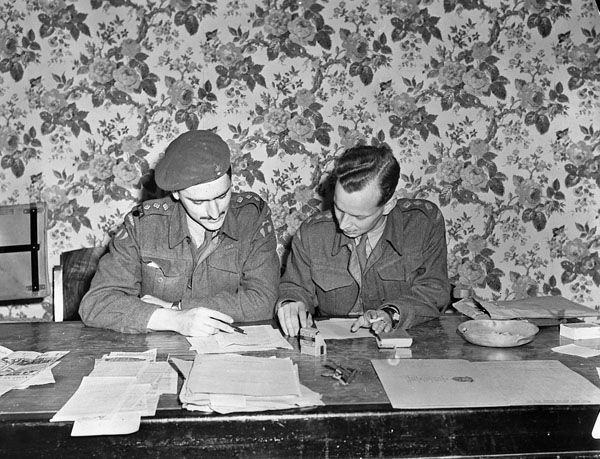 Captains Alan Duckett and Seth Halton censoring copy to be printed in the first issue of the Maple Leaf newspaper, Caen, France, 28 July 1944.